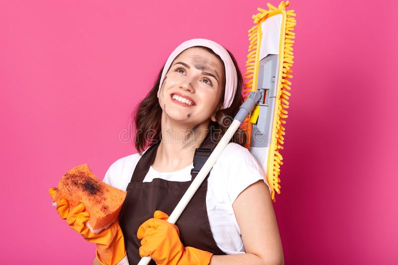 Close up portrait of smiling happy housewife looking up, holding broom and sponge in both hands with gloves. Delighted brunette royalty free stock images