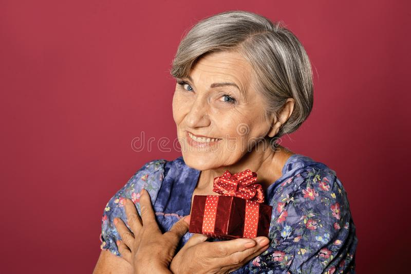 Close up portrait of smiling senior woman posing with present stock photos