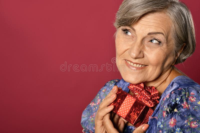 Close up portrait of smiling senior woman posing with present royalty free stock photography
