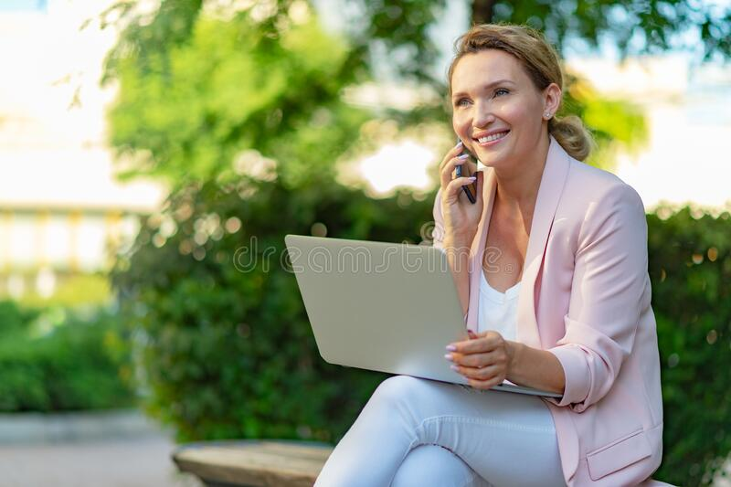 Close-up portrait of a smiling woman calling by phone on the street.  Happy businesswoman is using smart phone, outdoors. Cheerful stock image