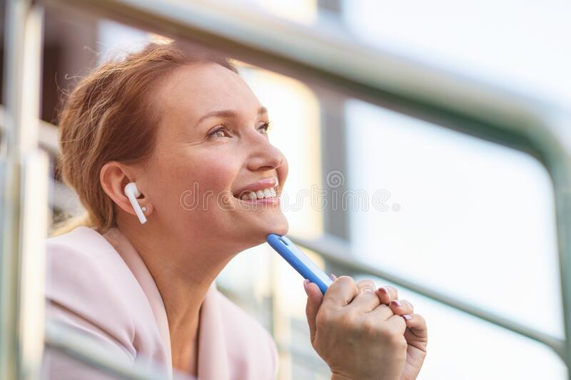 Close-up portrait of a smiling woman with smartphone on the street.  Happy businesswoman is using phone, outdoors. Cheerful stock photography
