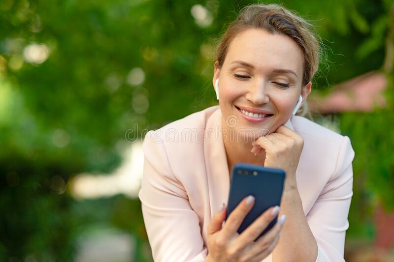 Close-up portrait of a smiling woman with smartphone on the street.  Happy businesswoman is using phone, outdoors. Cheerful stock photos