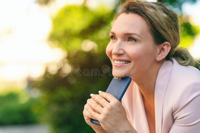 Close-up portrait of a smiling woman with smartphone on the street.  Happy businesswoman is using phone, outdoors. Cheerful stock images
