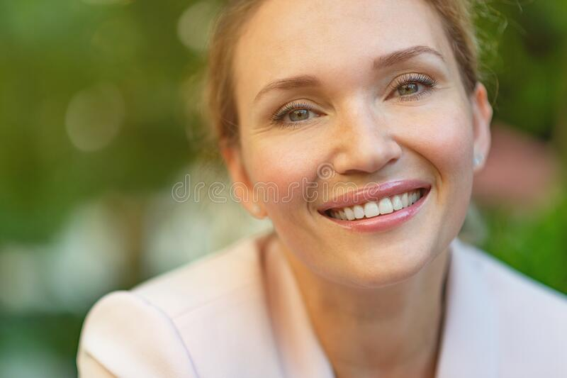 Close-up portrait of a smiling woman on the street. Happy woman`s face closeup, outdoors. Happy businesswoman in a light jacket royalty free stock photos