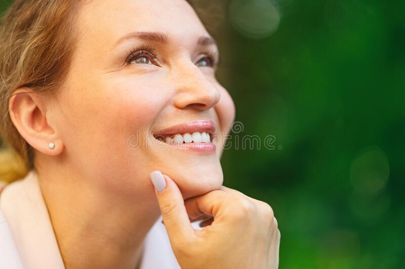 Close-up portrait of a smiling woman on the street. Happy woman`s face closeup, outdoors. Happy businesswoman in a light jacket royalty free stock image