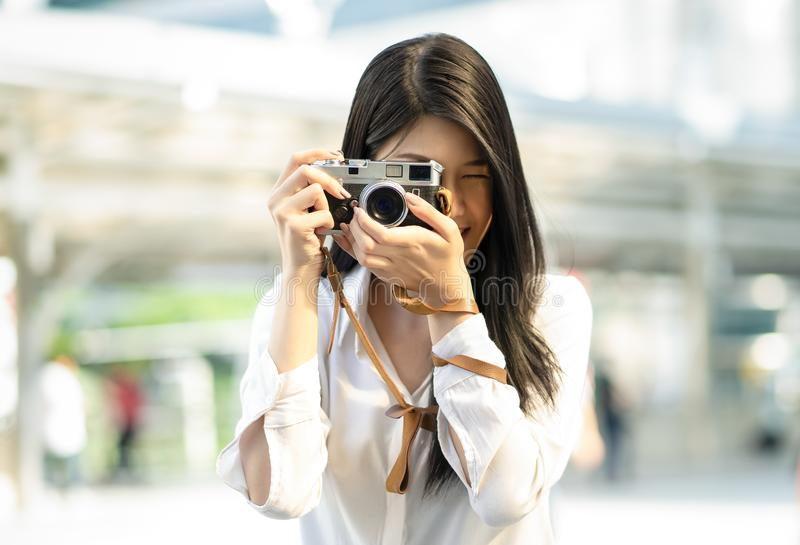 Close up portrait of a smiling woman taking photos with retro film camera on the field in the city royalty free stock image