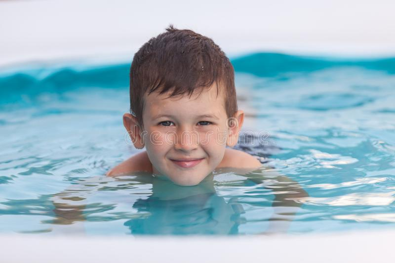 Close up portrait of a smiling young boy in the pool. Vacations concept royalty free stock photo