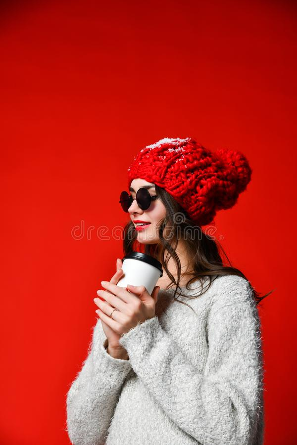 Close up portrait of a smiling young girl in hat holding take away coffee cup stock image