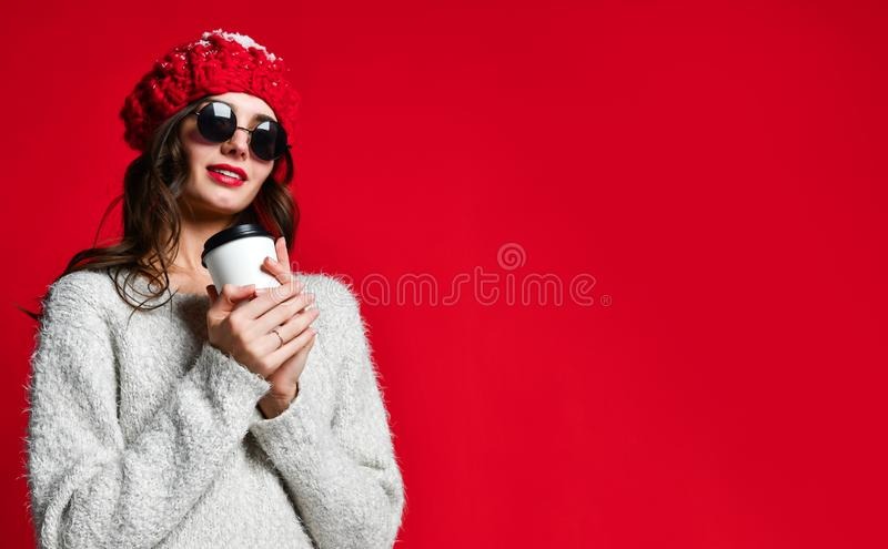 Close up portrait of a smiling young girl in hat holding take away coffee cup royalty free stock images