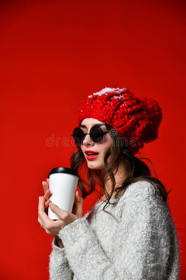 Close up portrait of a smiling young girl in hat holding take away coffee cup royalty free stock photos