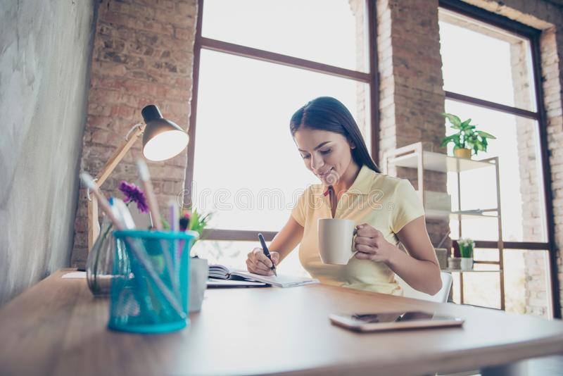 Close up portrait of a smiling young hispanic girl is drinking t. Ea at the office and making notes in nice light work station royalty free stock image