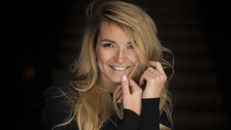 Close-up portrait of smiling young woman with curly blond hair.  stock photography