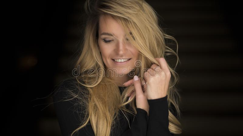 Close-up portrait of smiling young woman with curly blond hair.  royalty free stock photo