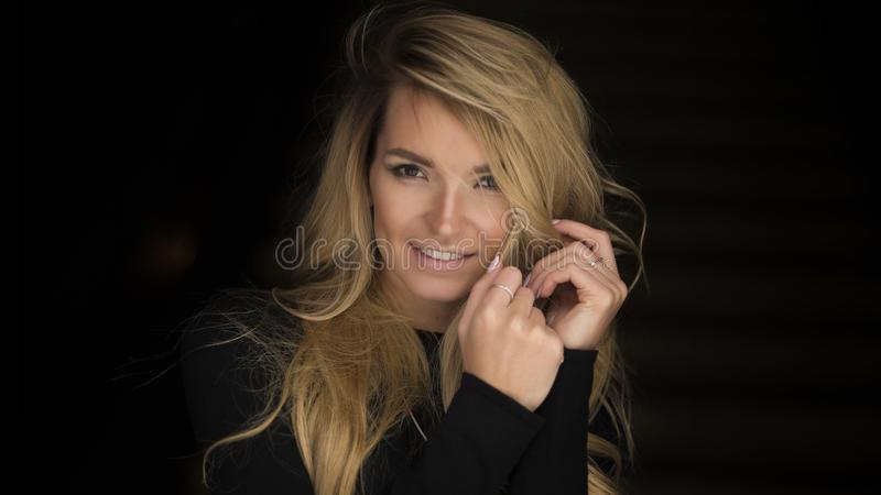 Close-up portrait of smiling young woman with curly blond hair.  stock photo