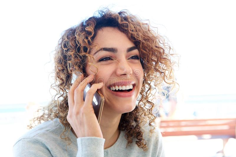 Close up smiling young woman talking on cellphone outside royalty free stock photography