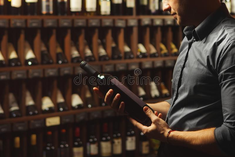Close up portrait of sommelier holding wine bottle on wine cellar background. stock photography