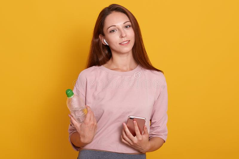 Close up portrait of sporty fit woman wearing rosy shirt, holding water bottle and looks smiling at camera, posing isolated onver royalty free stock image