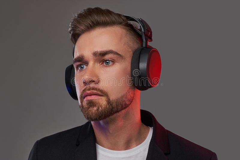 Close-up portrait of a stylish bearded man with hairstyle listening to music in headphones. stock photo