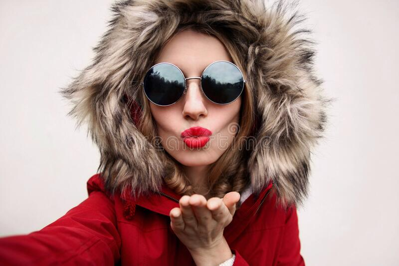 Close up portrait of stylish cool woman blowing red lips sending sweet air kiss stretching hand for taking selfie. Wearing red jacket with fur hood stock photo