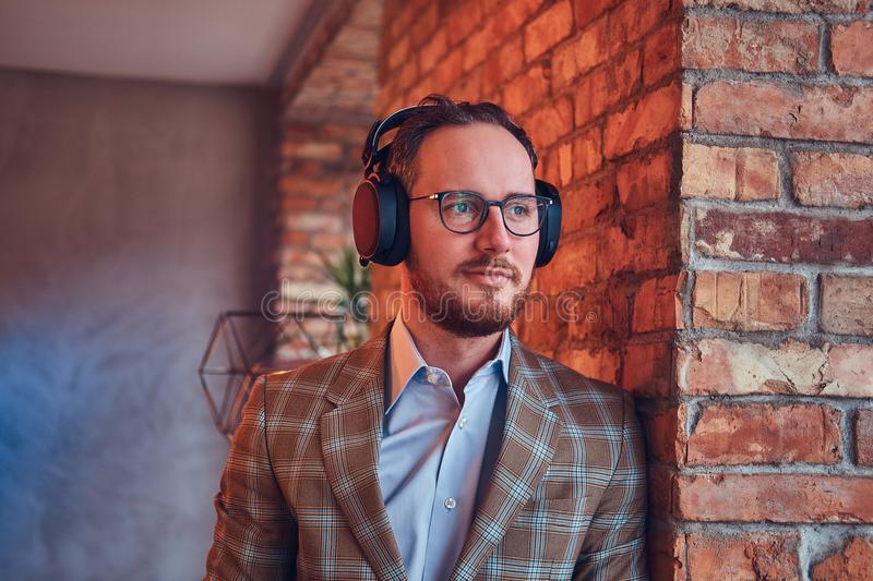 Close-up portrait of a stylish man in a flannel suit and glasses listening music. royalty free stock photos