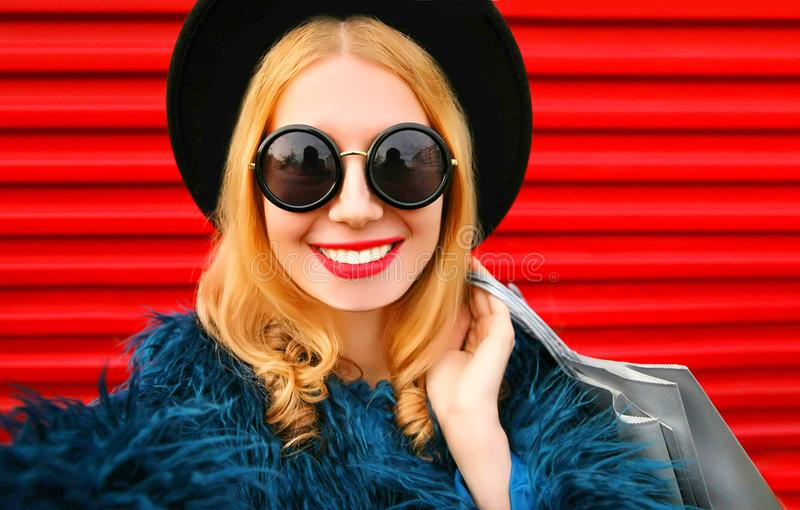 Close up portrait of stylish smiling woman stretching hand for taking selfie with shopping bags, stylish female model royalty free stock image