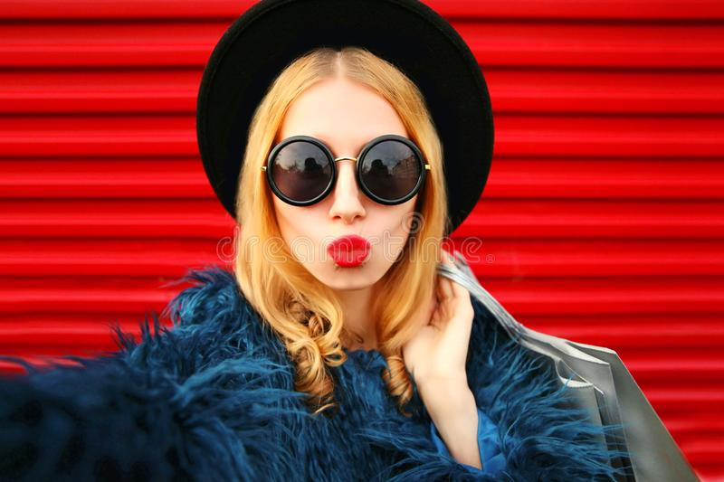 Close up portrait of stylish woman blowing red lips sending sweet air kiss stretching hand for taking selfie with shopping bags royalty free stock photography