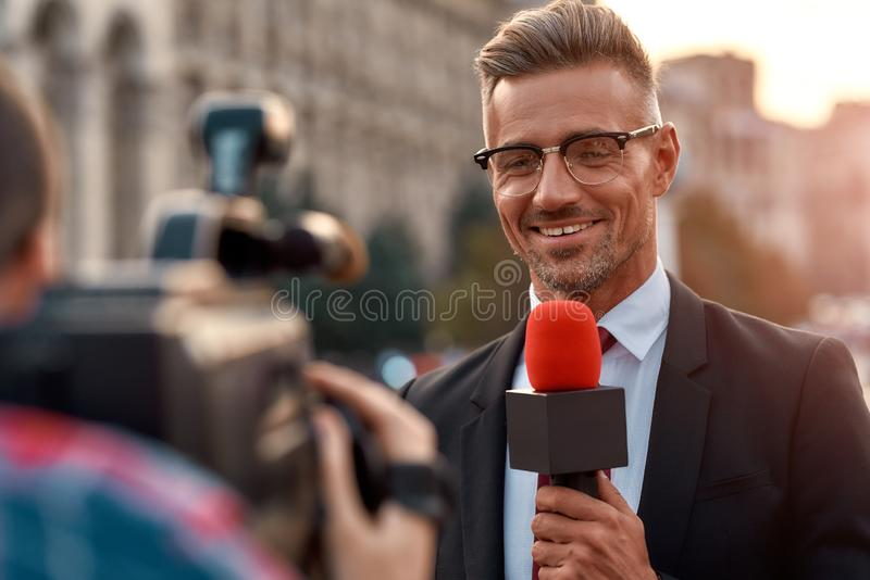 Better Than Ever. Professional reporter presenting the news on urban street. Journalism industry, live streaming concept stock photography