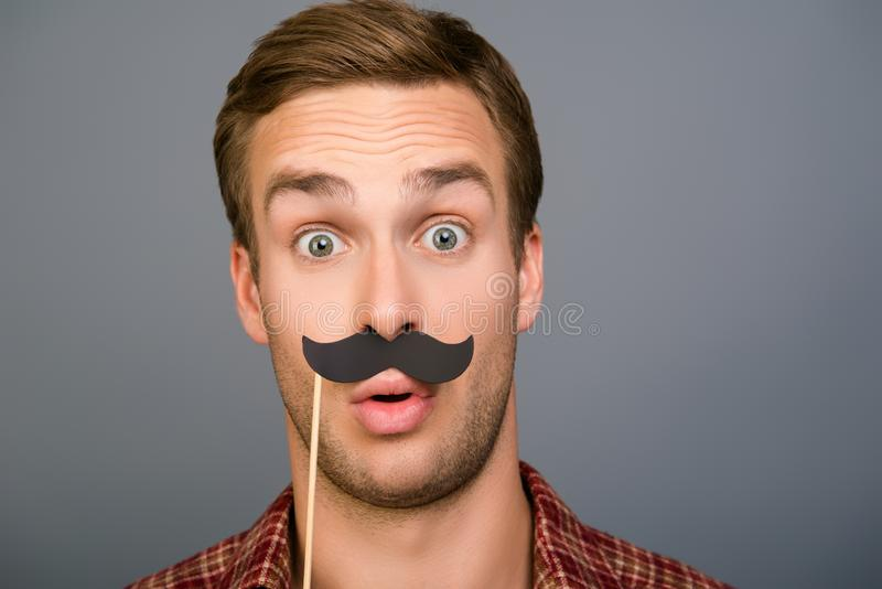 Close up portrait of surprised funny man holding paper mustache stock photo
