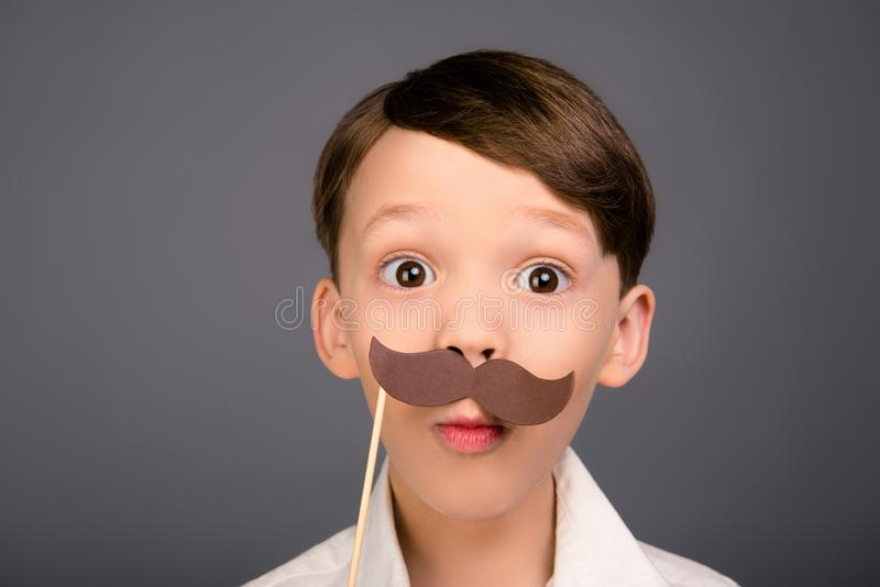 Close up portrait of surprised funny schoolboy holding paper mustache stock image