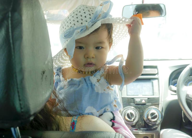 Close up portrait of sweet and adorable Asian Chinese baby girl in beautiful hat hold by her mum inside a car in family lifestyle royalty free stock photo