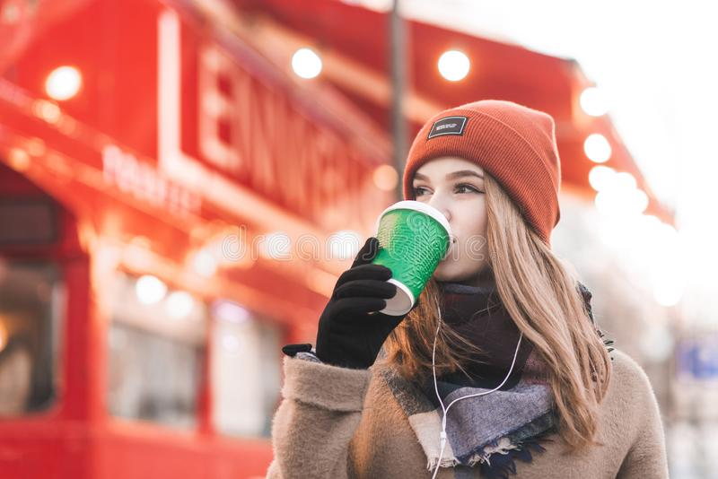 Close-up portrait of a sweet lady in warm clothes drinks coffee in a bright red city background. Beautiful girl in a cap drinking. Coffee with a cup on the stock images