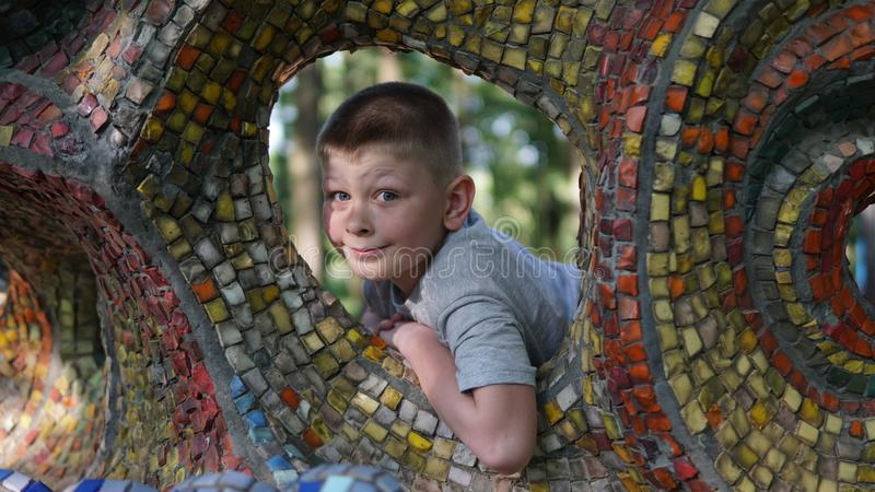 Close up portrait of teen boy. Funny cute teenager looking through a hole. Close up portrait of caucasian teen boy. Funny cute teenager in summer park at day stock photo