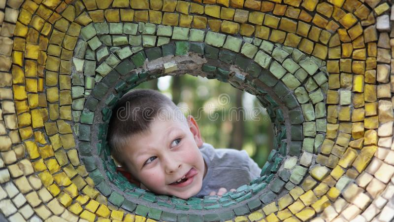 Close up portrait of teen boy. Funny cute teenager looking through a hole. Close up portrait of caucasian teen boy. Funny cute teenager in summer park at day royalty free stock photo