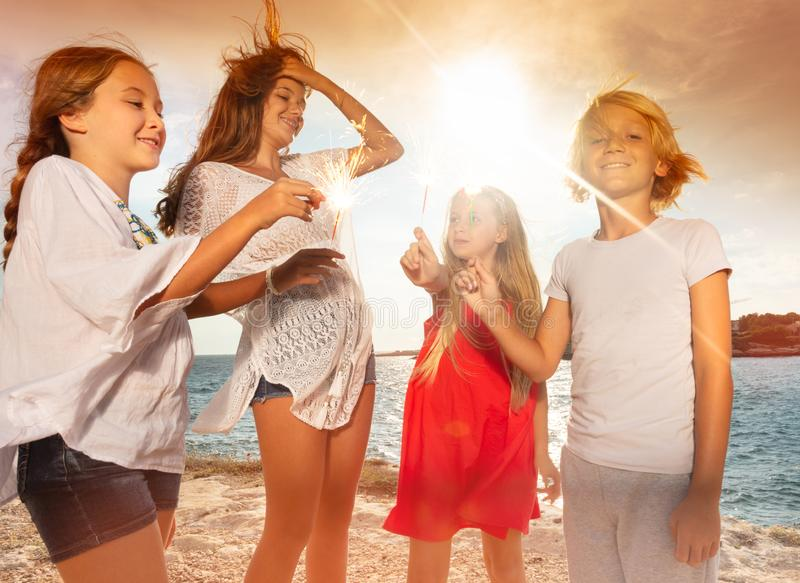 Happy teens holding sparklers during beach party royalty free stock photo
