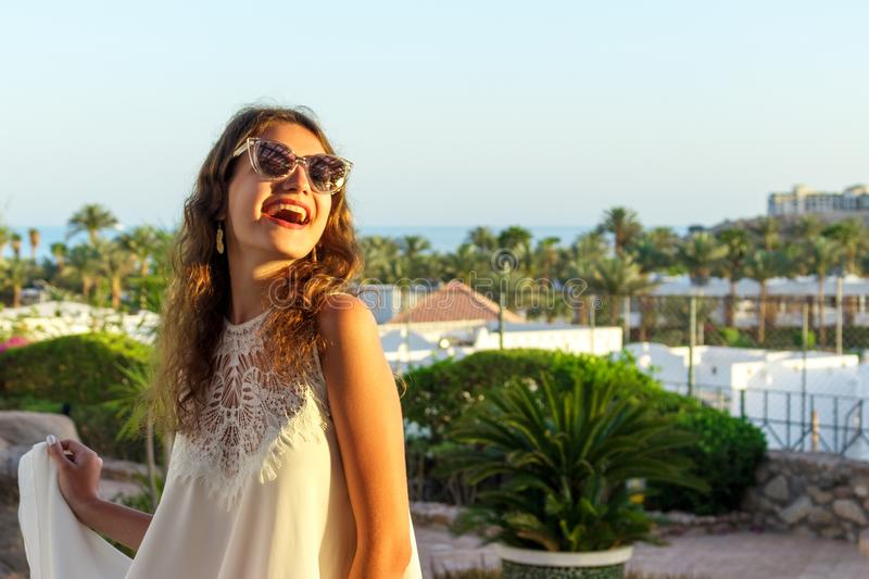 Close up portrait of a teenage girl in white dress and Sunglasses in a park during a sunny day, looking and smiling against the sk stock photo