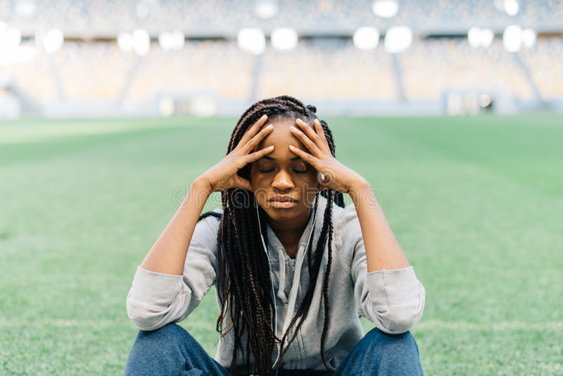 Close-up portrait of the thoughtful afro-american sportgirl sitting on the grass and leaning on the knees. stock image