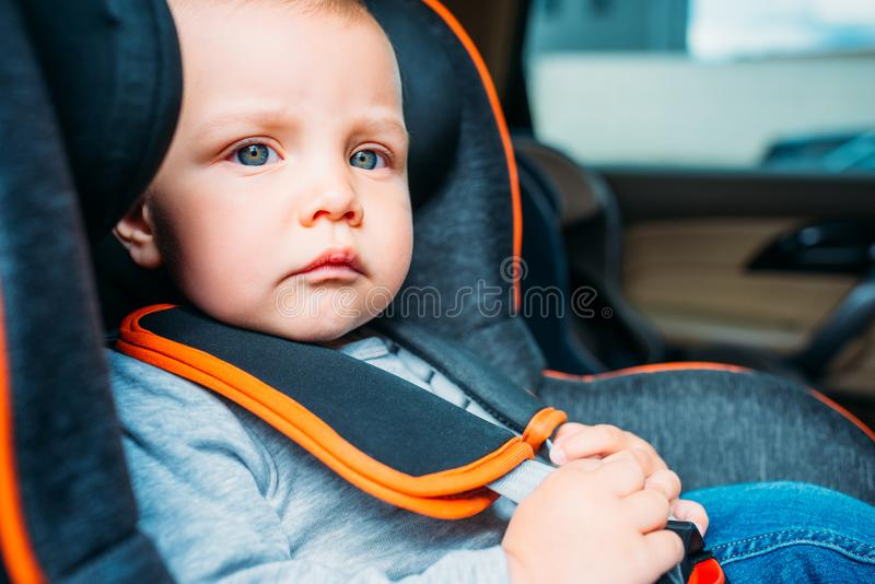 Close-up portrait of thoughtful little baby sitting in child. Safety seat in car and looking away stock images