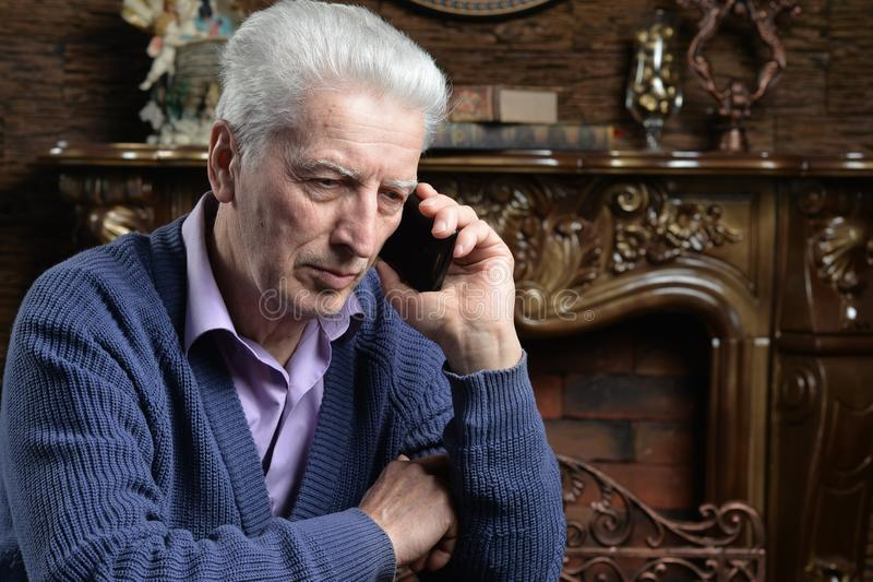 Close up portrait of thoughtful senior man with smartphone stock images