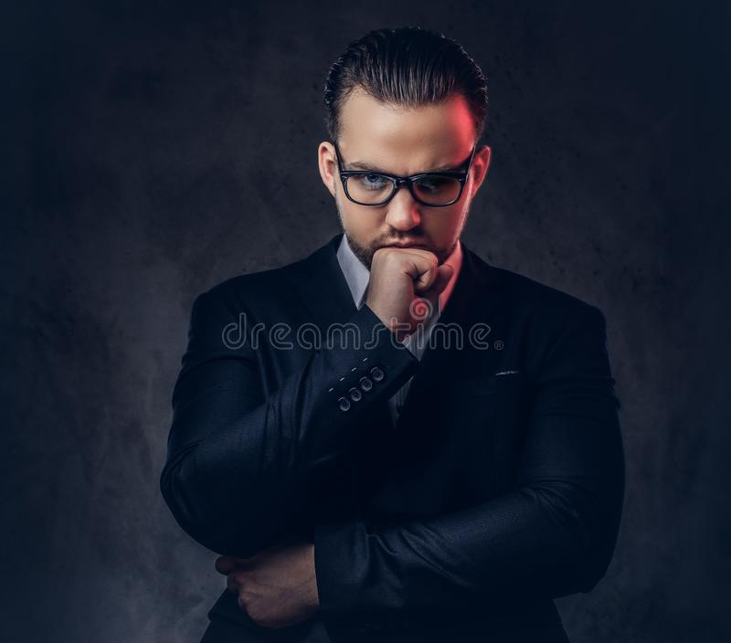 Close-up portrait of a thoughtful stylish businessman with serious face in an elegant formal suit and glasses on a dark royalty free stock image