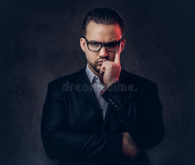 Close-up portrait of a thoughtful stylish businessman with serious face in an elegant formal suit and glasses on a dark stock photos