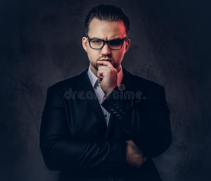 Close-up portrait of a thoughtful stylish businessman with serious face in an elegant formal suit and glasses on a dark stock images