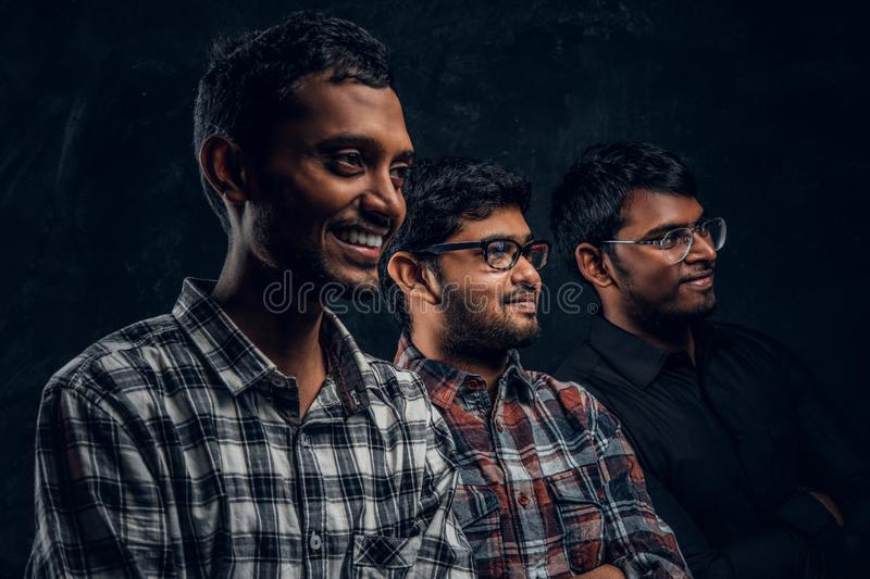 Close-up portrait of three happy Indian students wearing casual clothes against a dark wall. royalty free stock images