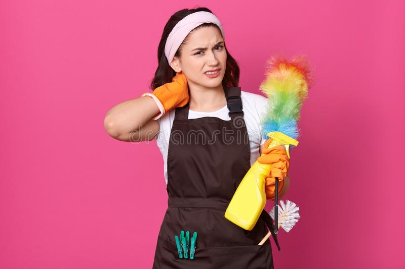Close up portrait of tired attractive young Caucasian woman, having pain in neck, wearing orange gloves and brown apron, standing royalty free stock image