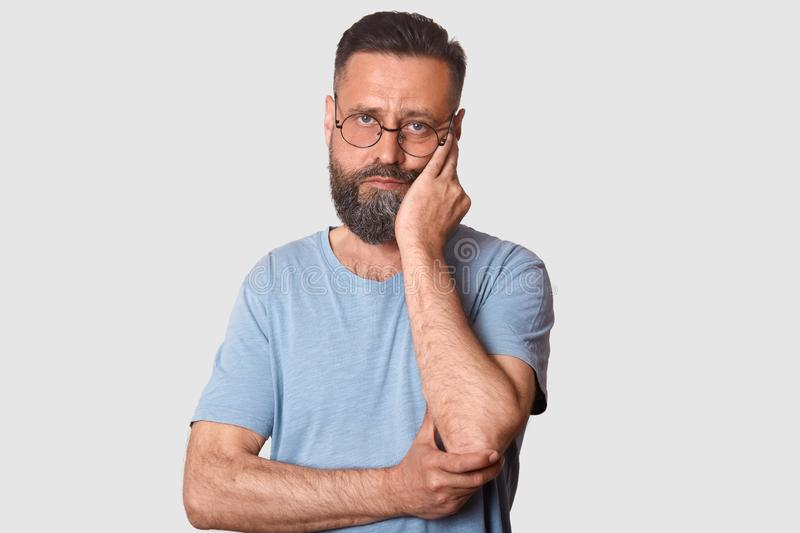 Close up portrait of tired calm man standing isolated over white background, looking directly at camera, touching his face with. One hand, being deeply upset stock images