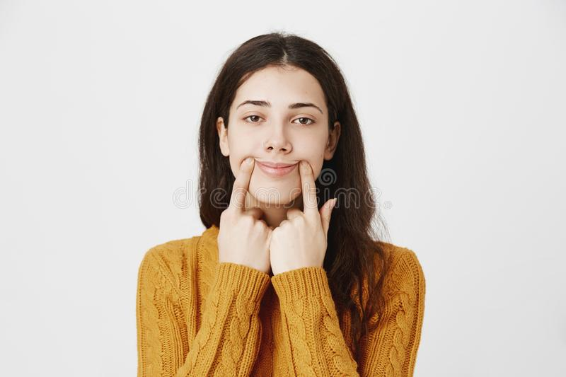 Close-up portrait of tired and gloomy caucasian pierced girl stretching mouth with fingers, making fake smile while royalty free stock photos