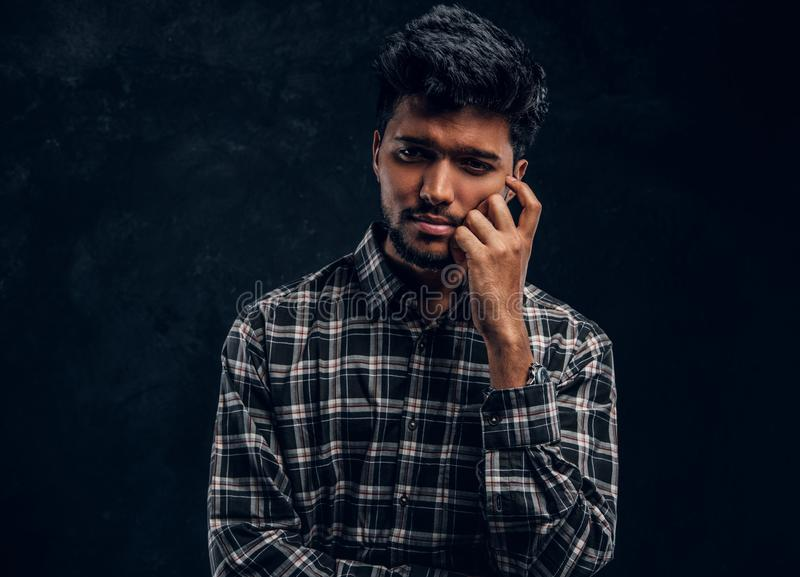 Close-up portrait of a tired Indian man wearing a plaid shirt. Studio photo against a dark textured wall stock photos