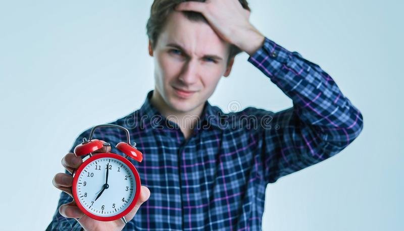 Close-up portrait of a troubled young man holding alarm clock isolated over white background. royalty free stock image