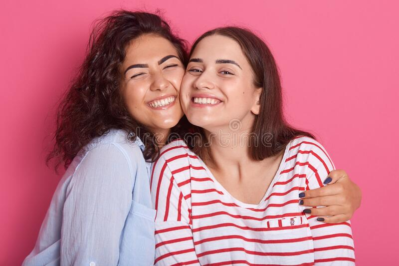 Close up portrait of two attractive caucasian smiling women iposing solated on over pink studio background, brunettef emales stock image