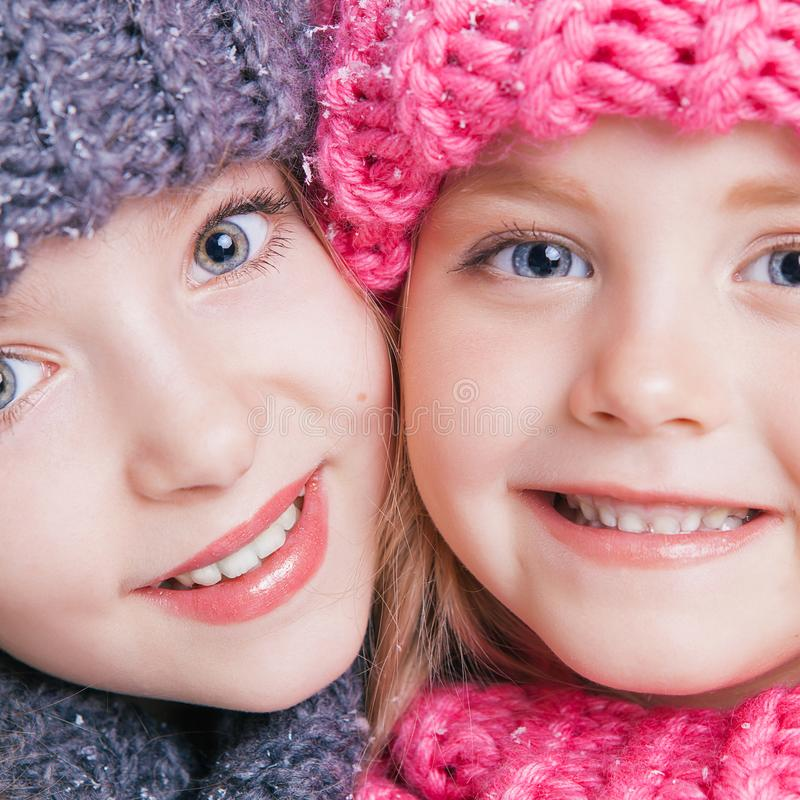 Close-up portrait of two cute little sisters in winter clothes. Pink and grey hats and scarfs. Family stock image