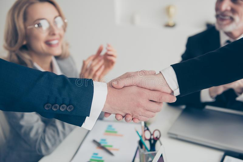 Close up portrait of two elegant classic partners making handshake above signed contract in work place, workstation, smiling stock image